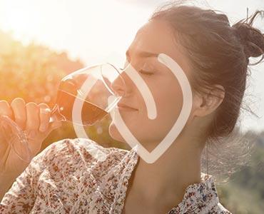 Femme dégustant un verre de vin rouge dans une vigne