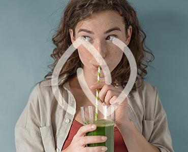 Jeune femme buvant un jus détox
