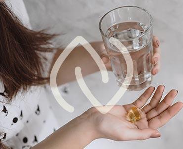 Jeune femme tenant une pilulle de vitamine D