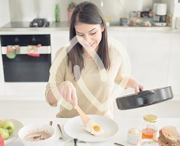 Jeune femme cuisinant un oeuf au plat